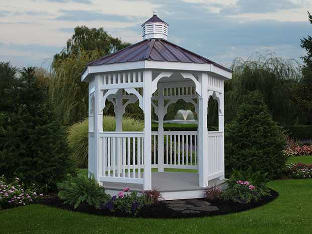 Small octagonal white vinyl gazebo with a bronze roof sitting in a flowerbed