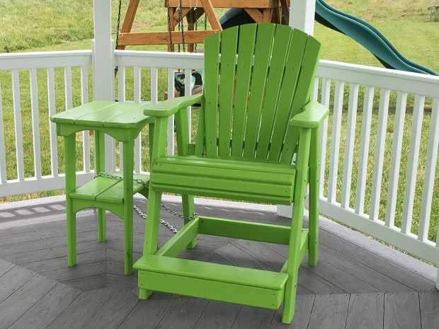 A lime green balcony chair and end table sitting in a gazebo