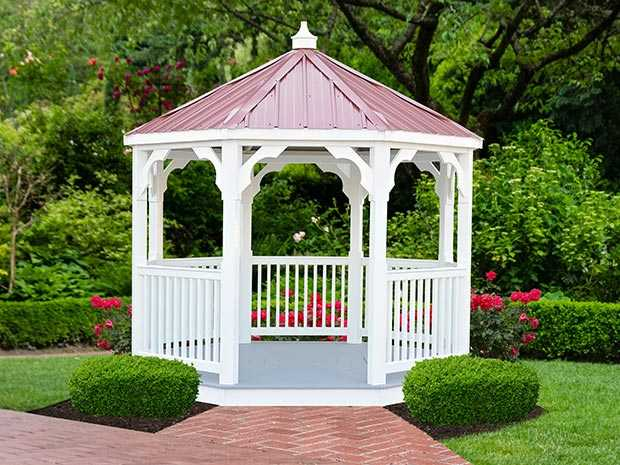 a White vinyl value gazebo with a burgundy roof surrounded by beautiful landscaping